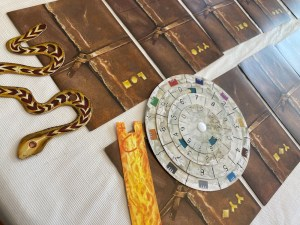 Assorted game components including a paper snake and a solution wheel.