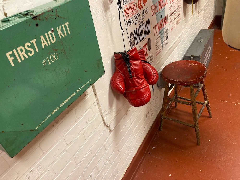 First aid kit, boxing gloves, and a stool in a boxing club.