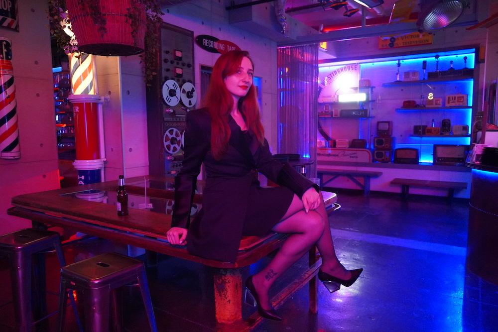 Magician Rachel Wax posing on a table.