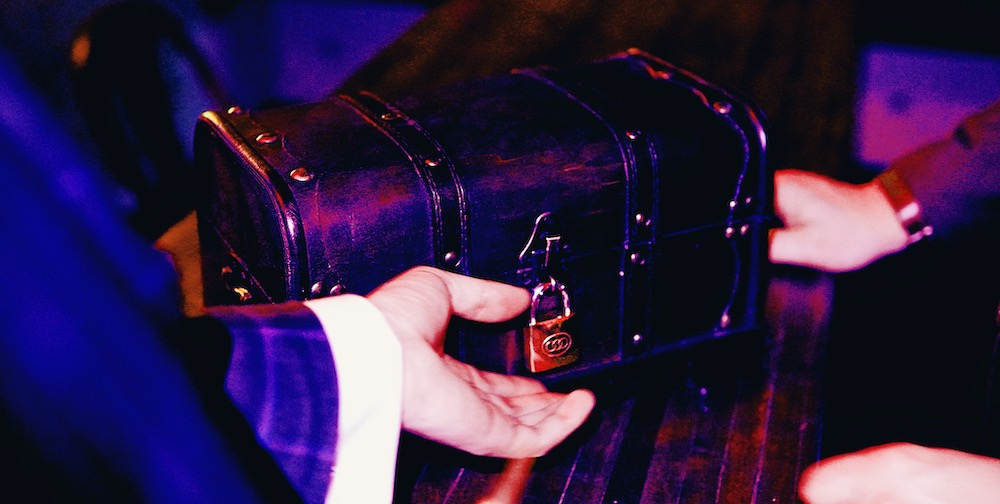A hand reaching out for a small chest secured with a padlock.