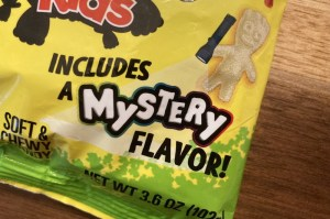 """Closeup of packaging shows a white gummy character holding a flashlight that is illuminating the words, """"includes a mystery flavor!"""""""