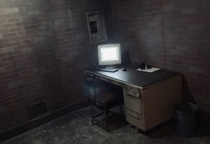 A computer desk in a dim room with an old CRT monitor illuminated.
