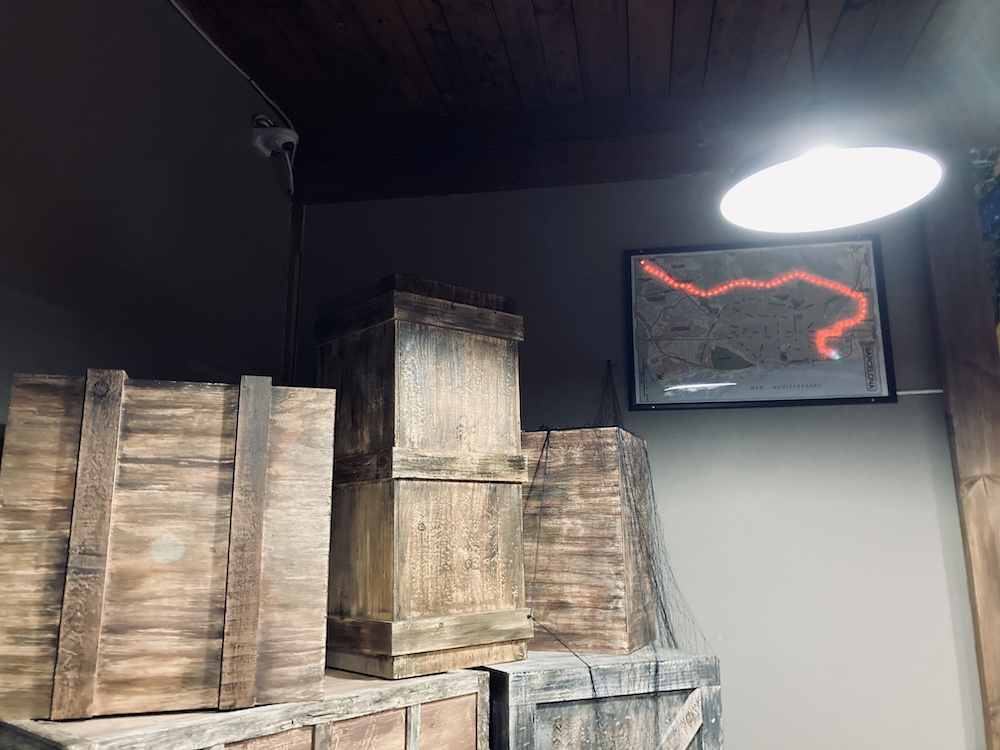 Warehouse area with a lot of large wooden crates and a map with a glowing train line path.