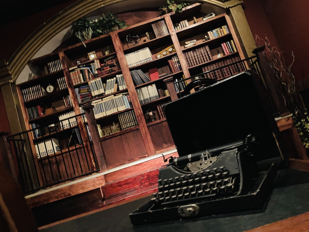 An old typewriter in the foreground, a beautiful bookcase wall in the background.