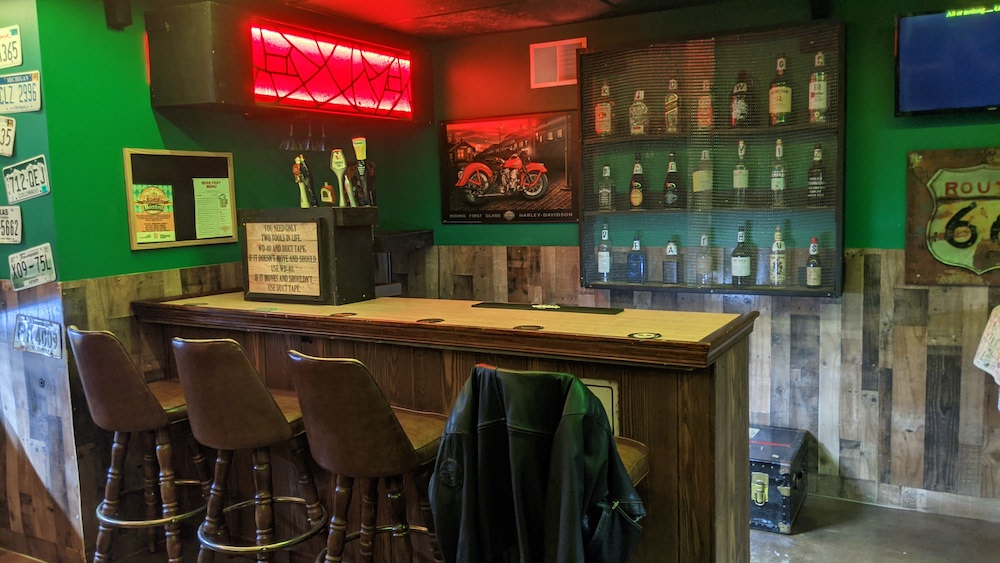 The bar top and seats in an old dive bar.