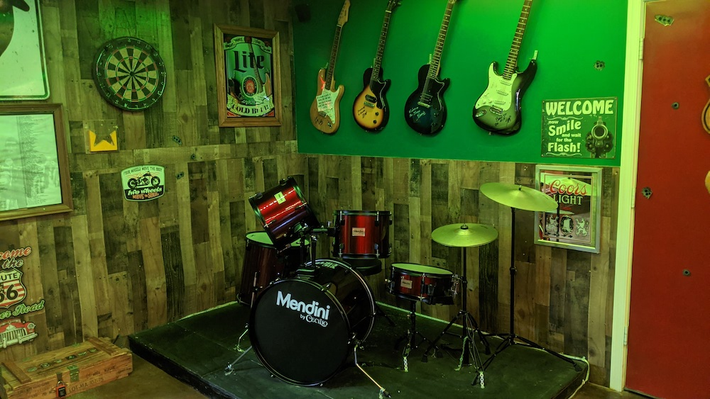 A drum kit on a small riser in a dive bar. The wall beyond it has a dart board, beer ads, and 4 electric guitars hanging.