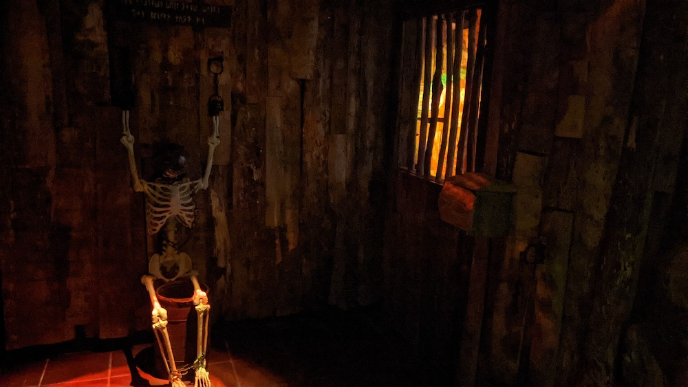 A skeleton chained to the wall in a wooden cell.