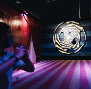 A player throwing a ball at an elaborate rotating target.