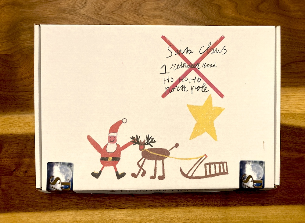 White box for Dear Santa depicts a child's artwork of Santa, addressed to the North Pole.