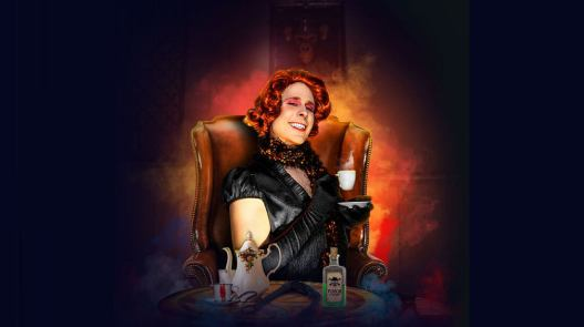 a man in drag, wearing a red wig sitting in an easy chair holding a teacup. on the coffee table in front is a tea pot and a bottle of poison.