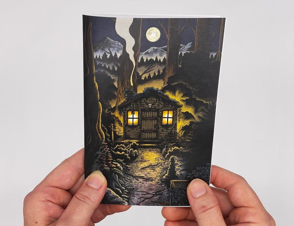 Booklet cover art depicts a spooky cabin in the woods at night, under a full moon.
