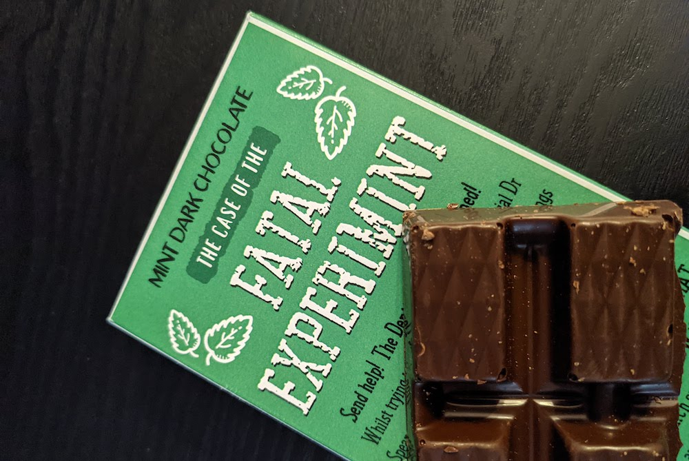 """A piece of chocolate resting on its green packaging, labeled, """"Mind Dark Chocolate, The Case of the Fatal Experiment."""""""