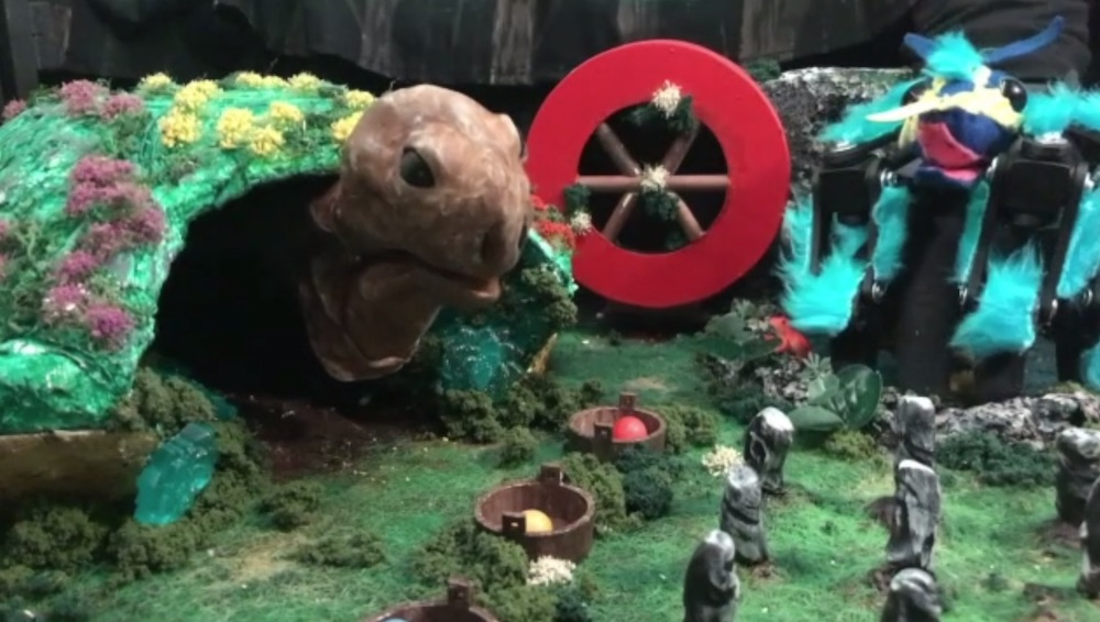 A large turtle puppet in a diorama beside a bule spider puppet.