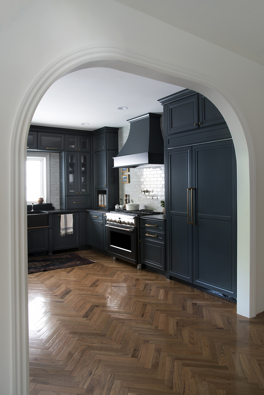 Archway into Navy Kitchen with Herringbone Wood Floors ...