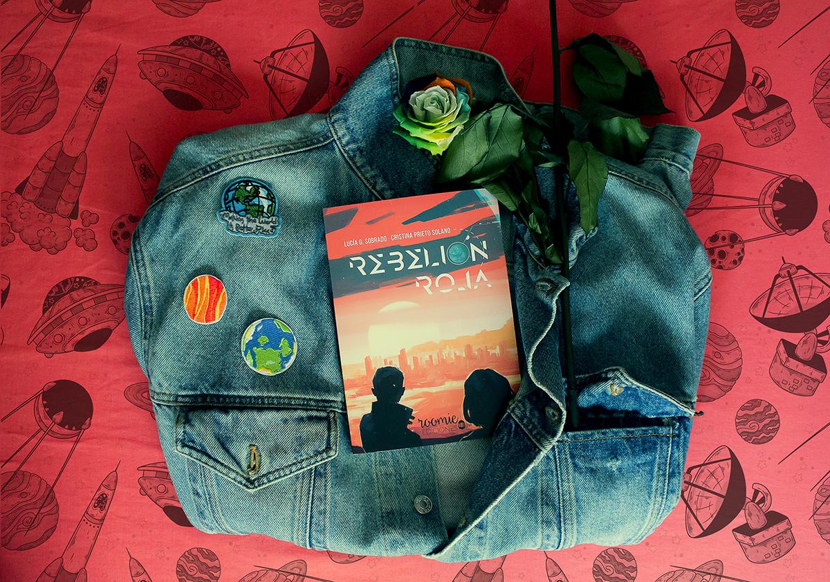 Sobre un fondo rojo/rosa con motivos espaciales, hay una chaqueta doblada. En ella hay tres parches (la Tierra dos veces y Marte) y el libro de Rebelión Roja. También se puede ver un tallo de rosa y una flor multicolor.