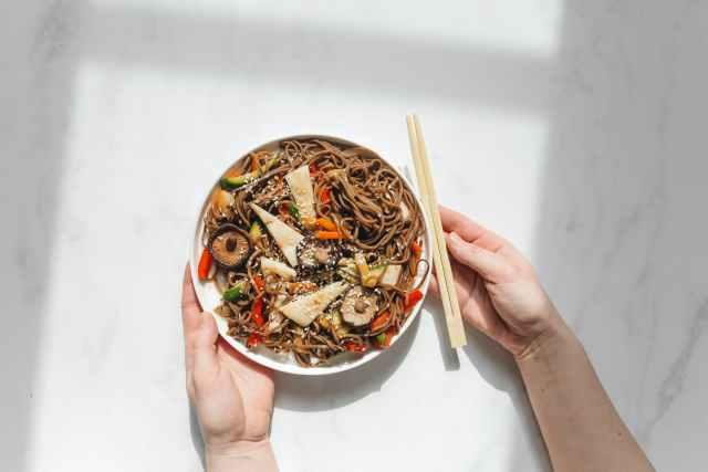 person holding plate with noodle dish and chopstick