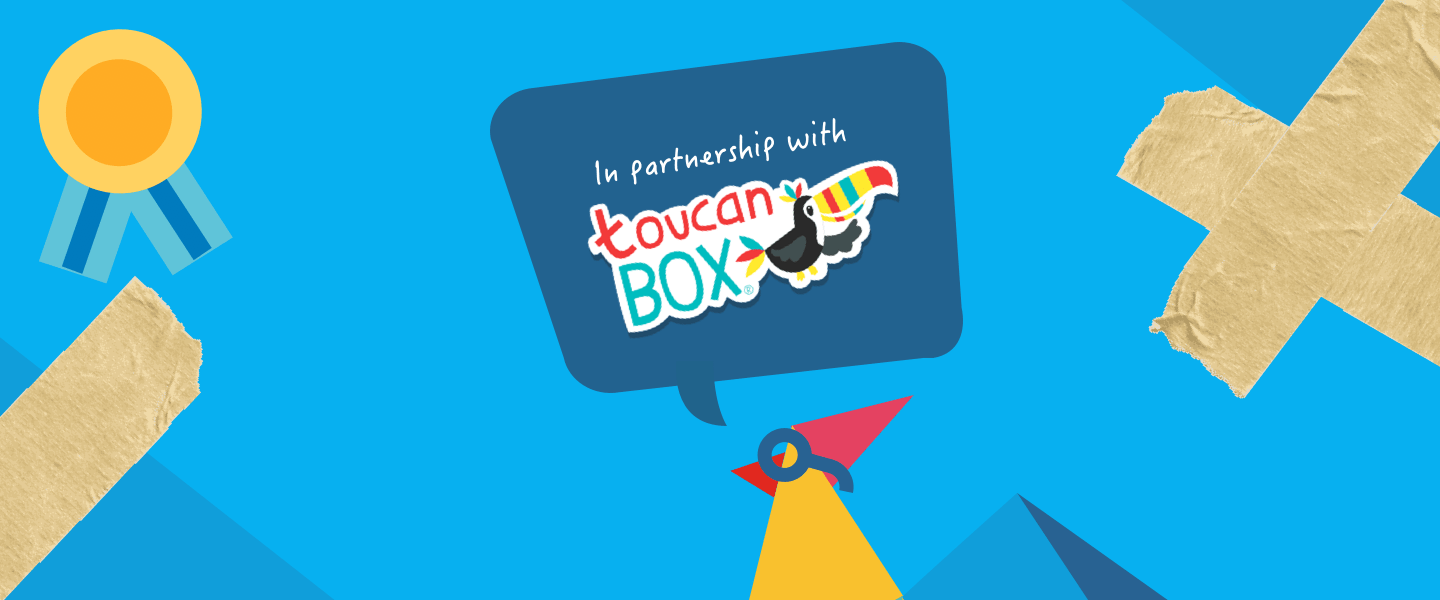 The RoosterMoney logo wearing glasses with a speech bubble coming from its beak stating it's in partnership with Toucan Box, with sticky tape and a gold medal decorating the sides against a blue origami background