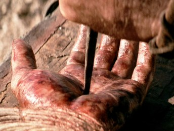 """The movie """"The Passion of the Christ"""", directed by Mel Gibson. Seen here, the left hand of James Caviezel as Jesus, during crucifixion. Initial theatrical release February 25, 2004. Screen capture. © 2004 Icon Distribution, Inc. Credit: © 2004 Icon Distribution / Flickr / Courtesy Pikturz. Image intended only for use to help promote the film, in an editorial, non-commercial context."""