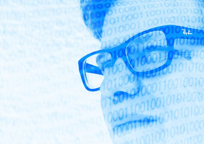 Man with glasses behind binary code