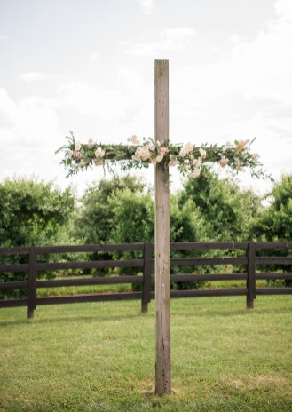 wooden cross decorated with flowers for a ceremony by an apple orchard