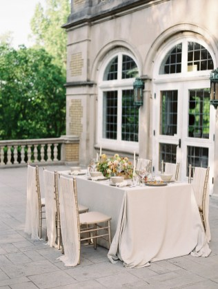 a banquet table on the balcony of Laurel Hall holds flowers and brass candle sticks.