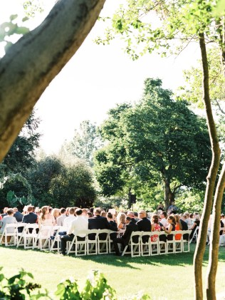 guests sit on chairs on the beautiful lawn at Yew Dell Botanical Gardens, a wedding venue in Kentucky