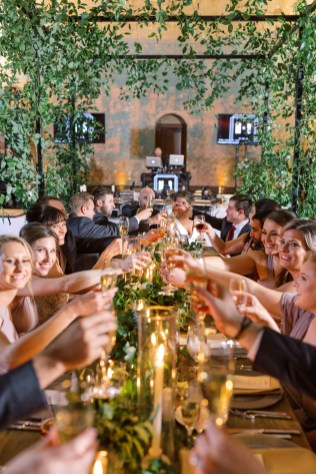 the wedding party celebrates with a cheers of their glasses underneath a greenery canopy