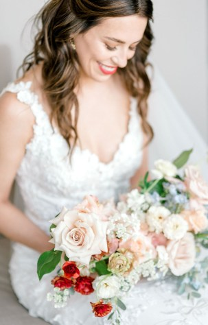 bride with bold red lip looks down on her bridal bouquet made by lexington wedding florist roots floral design featuring quicksand roses butterfly ranunculus lisianthus delphinium and orlaya