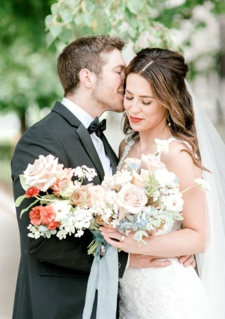 Bride smiles wide as the groom whispers in her ear holding her garden style wedding bouquet underneath a tree at hotel covington