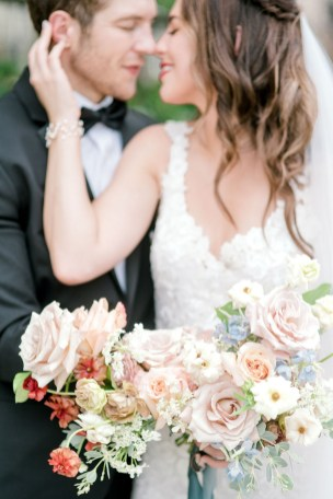 bride wraps her arm around the groom with pearl bracelet on while holding a flower bouquet designed by roots floral design a cincinnati wedding florist