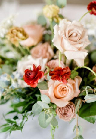 a close up photo of flowers in pink red and peach with greenery and a touch of blue
