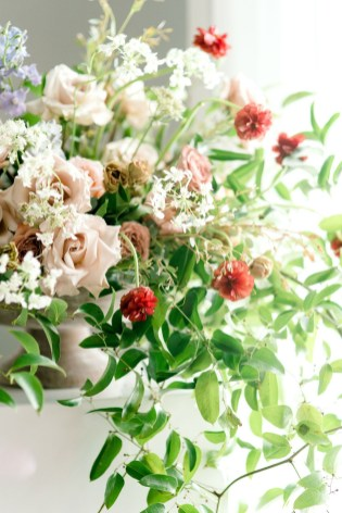 large and elevated centerpiece with overflowing flowers in red, pink, peach, white and bloom with greenery.