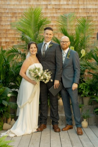 bride and groom stand with the officiant surrounded by potted plants and ferns at the factory events in cincinnati ohio flowers and plants by cincinnati wedding florist roots floral design