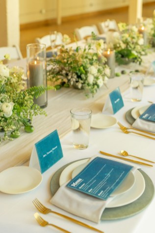textural white and green floral centerpieces line the white linen table with blue place cards and menus with concrete chargers and gold flatware at the factory events with cincinnati wedding florist roots floral design