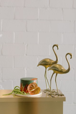 a green, orange, and yellow one tiered cake with anthurium and amaranthus flowers with brass gold flamingos