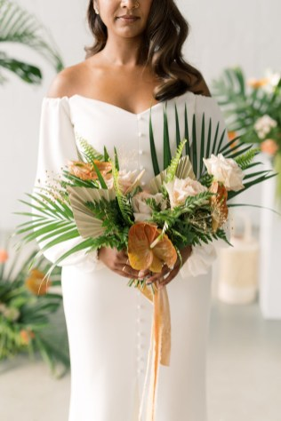 bride with nose ring wearing an off the shoulder wedding gown with buttons down the front holds tropical inspired bouquet by cincinnati wedding florist roots floral design with velvet ribbon