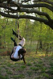 Shibari schoolgirl suspended in the park