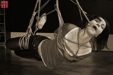 Low level shibari suspension by WykD Dave. Nina Russ enjoying expert shibari. Photo by Clover