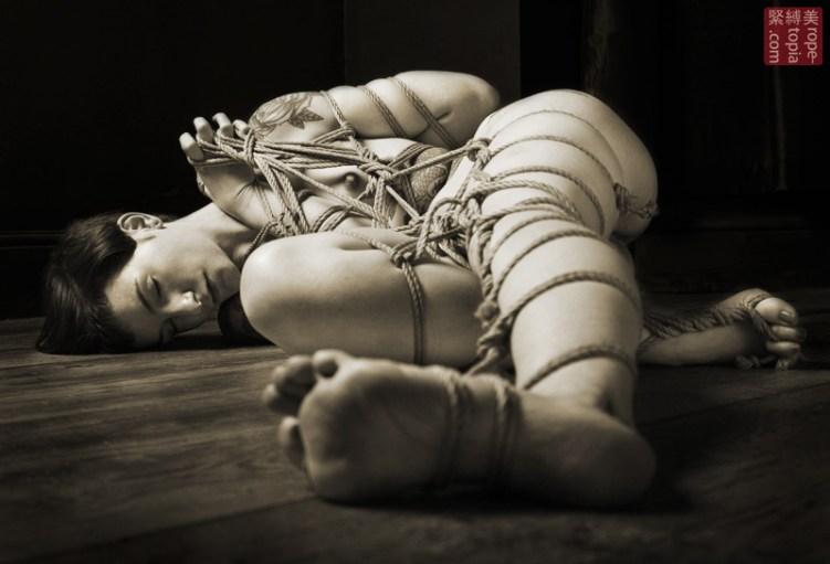 Asymmetric shibari floor bondage.