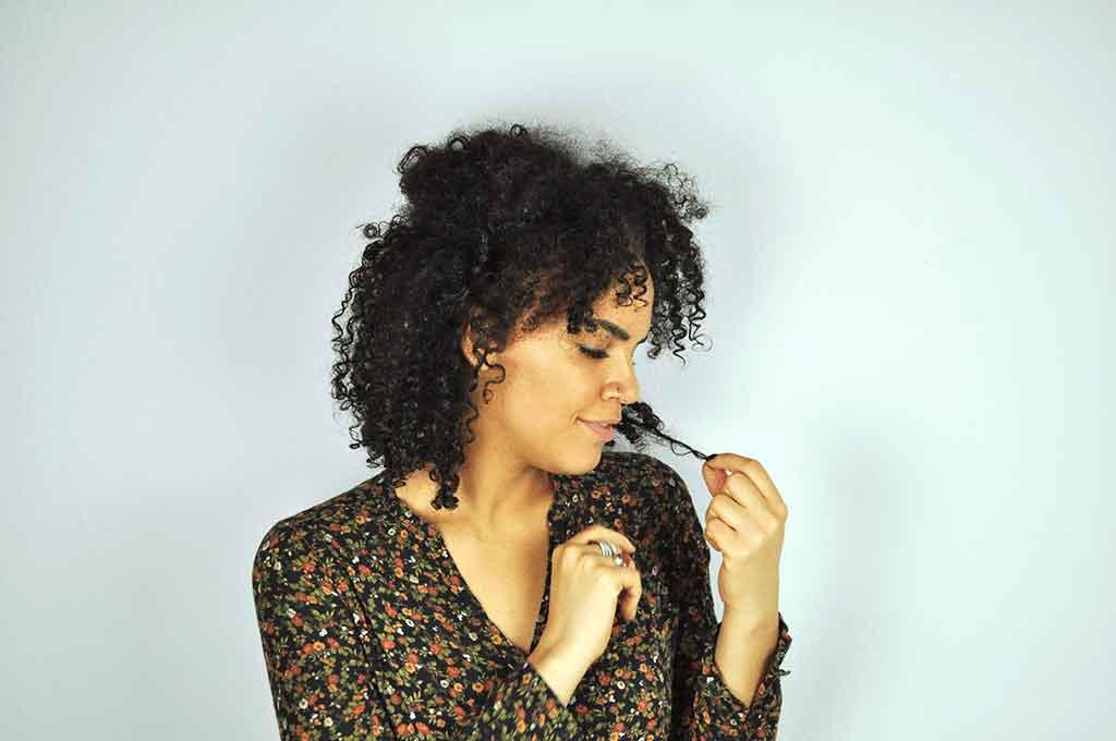 Eine junge Frau mit Afrolocken steht vor einer grauen Wand und betrachtet ihre Haarspitzen.