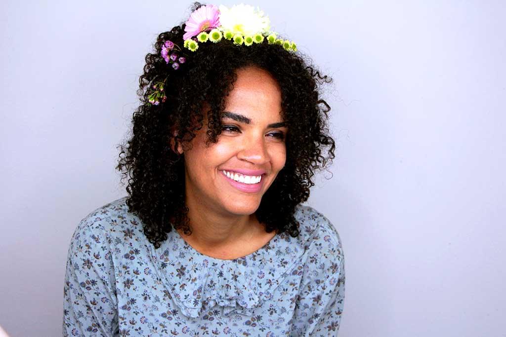 Auf dem Bild ist eine afrodeutsche junge Frau zusehen. Auf ihren Afrolocken befinden sich unterschiedliche Blumen, geformt zu einer Krone.