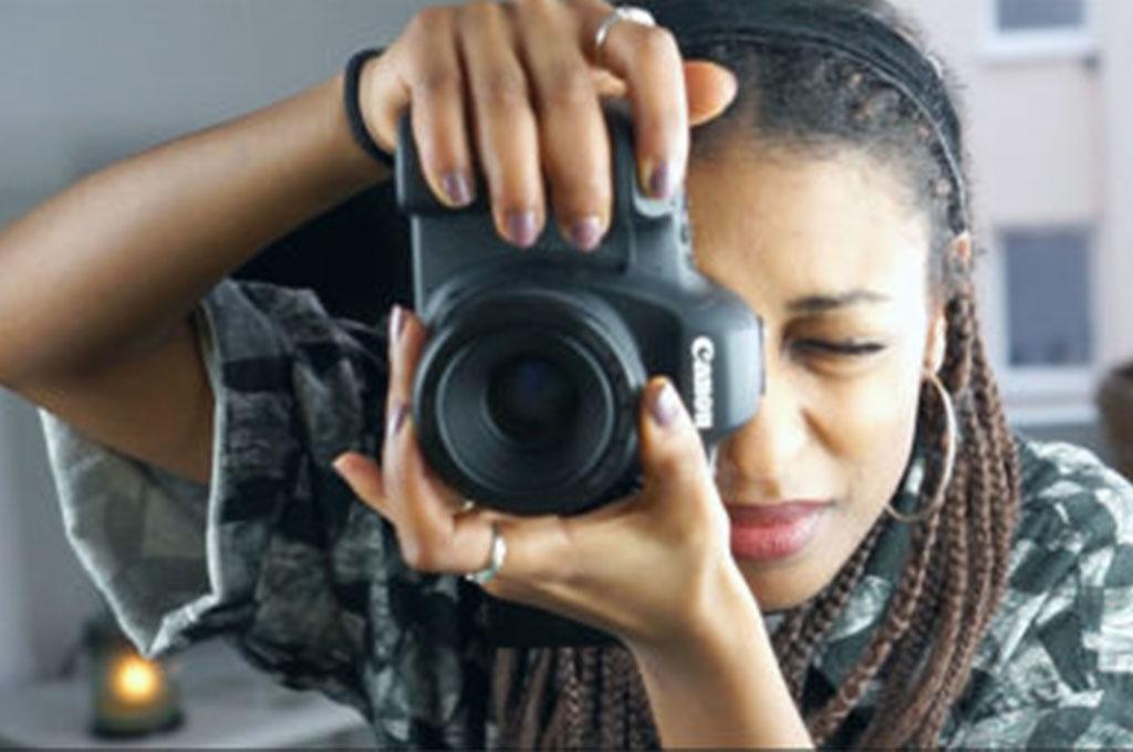 Eine junge Fotografin hält ihre Kamera in die Hand und schaut durch das Objektiv.