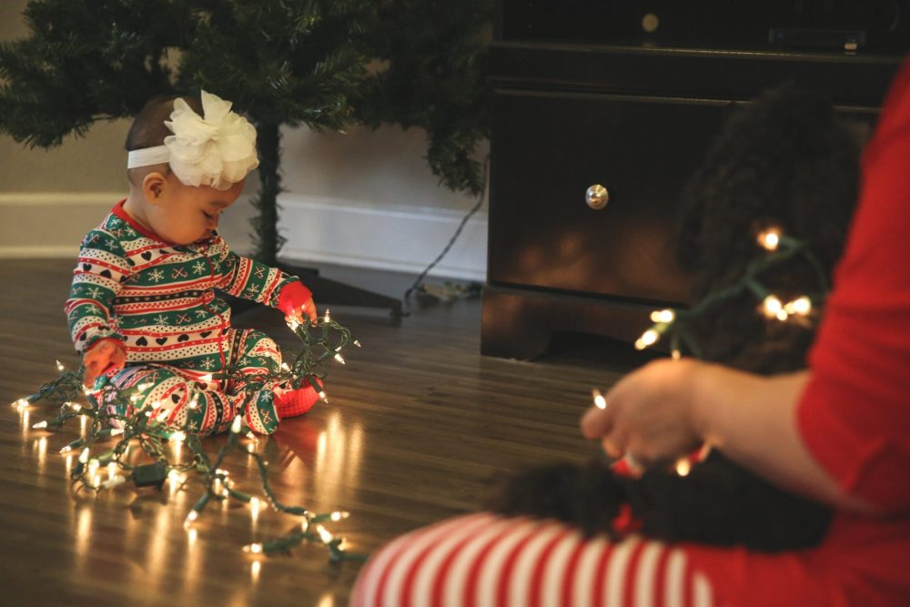 Holiday photos: Christmas photo of a baby in holiday pajamas playing with Christmas tree lights