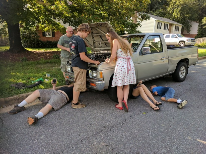 fixing an old junk truck in the road.