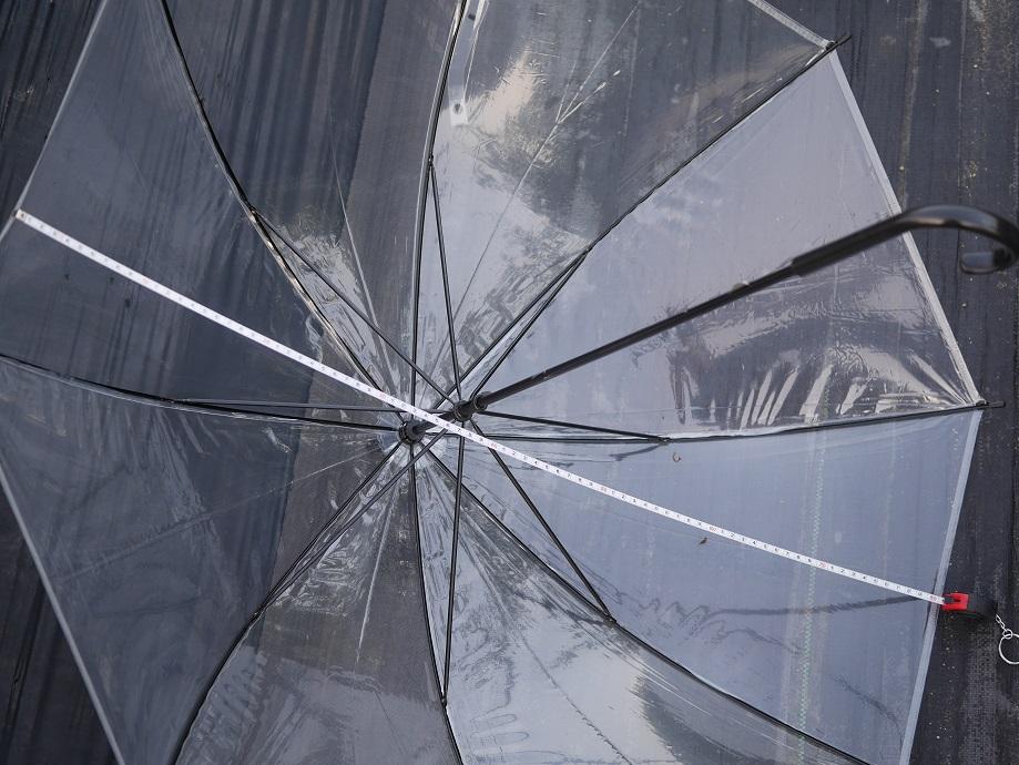 100円ショップで買ったビニール傘を広げた長さをメジャーで図っている写真。