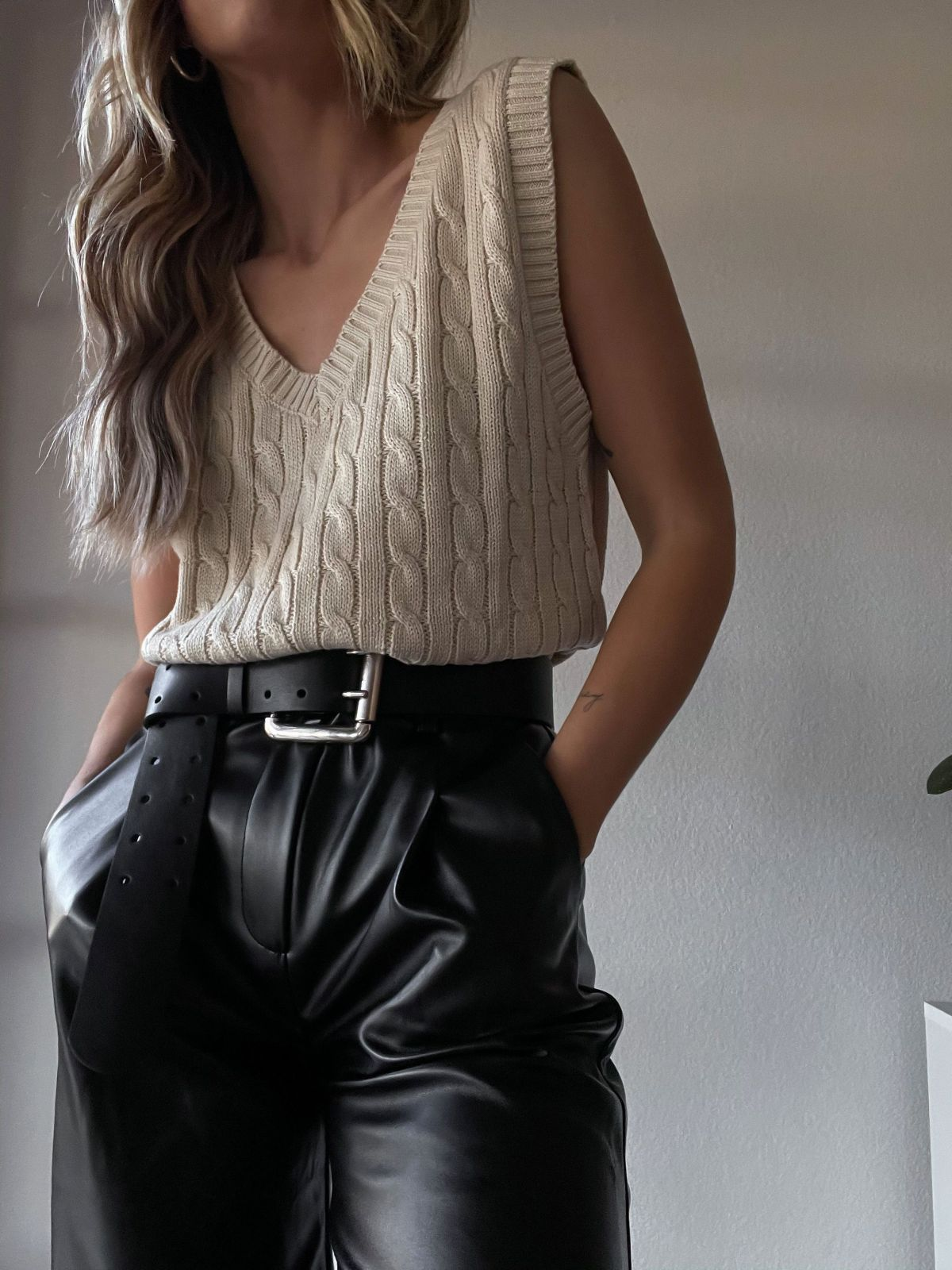Beige sweater vest with black leather pants