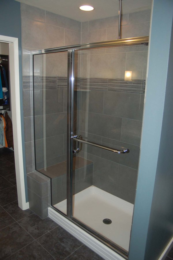 Door and Glass Tile Shower with Bench