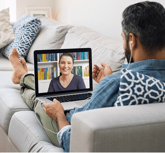 Person sitting on lounge using video telehealth platform to speak with his doctor