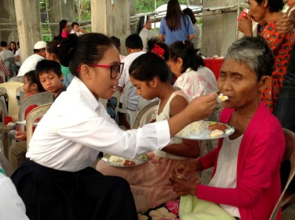 A postulant feeds a blind woman.