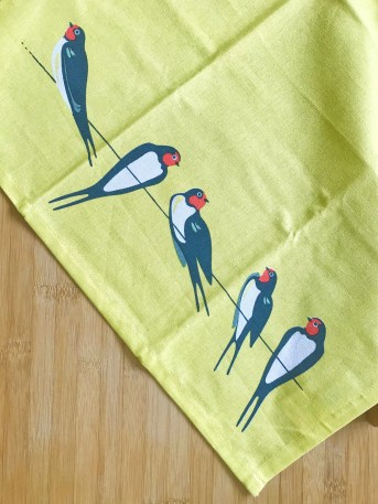 number 3 on the best Christmas gifts for foodies guide. A bright yellow tea towel with a graphic print of swallows lying on a bamboo kitchen work top